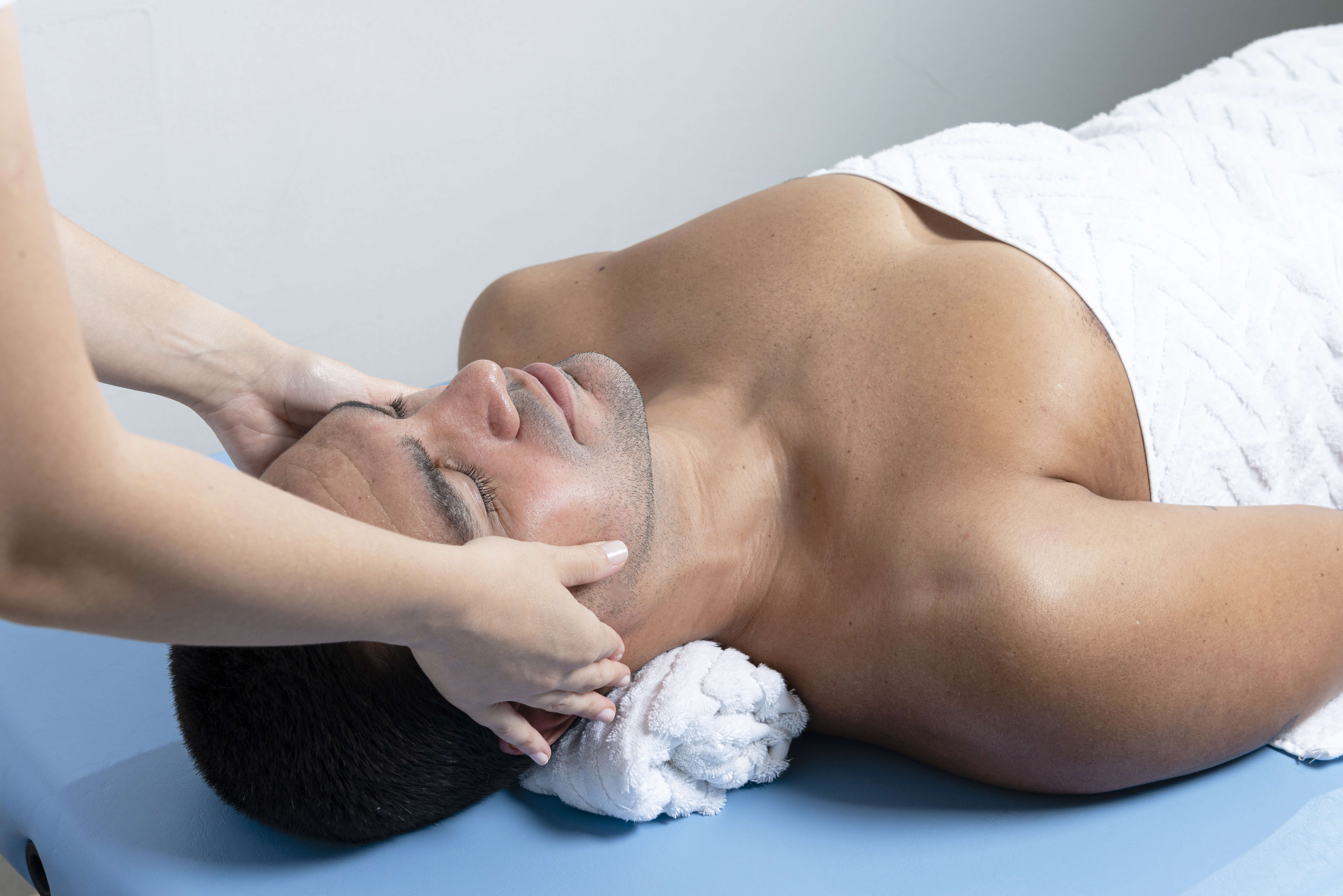 Modern rehabilitation physiotherapy. Therapist massaging man's face